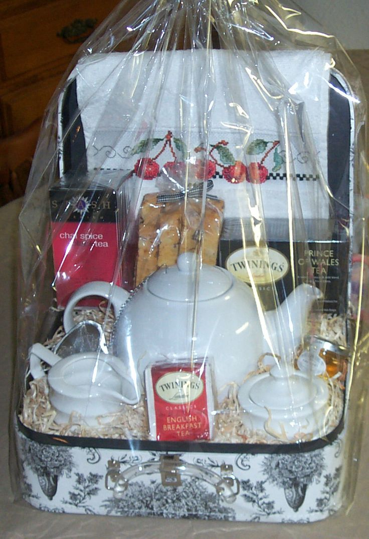 A tea themed gift basket with a hand -stitched tea towel and orange almond choco